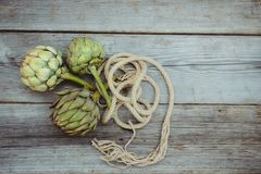 Top view Fresh green artichokes with braided rope on vintage wooden kitchen table. Farmer local market. Selective focus, Copy. Space. Flat lay stock photo