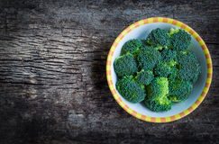 Top view. Fresh green broccoli on plate over wooden background. Stock Images