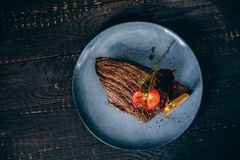Top view Fresh grilled meat steak with pear and tomato decoration. Black background.  royalty free stock photography