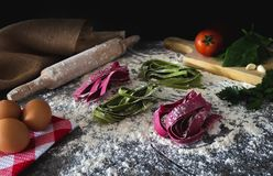 Colorful raw pasta witch flour, red and green stock photos