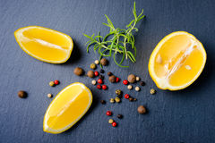 Top view of fresh lemon, rosemary and various peppers on slate background Stock Photography