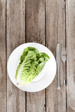 Top view of fresh letuce salad on plate with cutlery on wooden table. Healthy eating concept Royalty Free Stock Photo