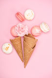 Top view of fresh macarons with waffle cones and Carnation flower on pink background Royalty Free Stock Photos
