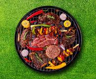 Top view of fresh meat and vegetable on grill placed on grass. Barbecue, grill and food concept Royalty Free Stock Photo