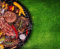 Top view of fresh meat and vegetable on grill placed on grass. Barbecue, grill and food concept Stock Photos