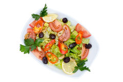 Top view of fresh Mediterranean salad with Pure olive oil. Overhead view of fresh Mediterranean salad with olives, tomatoes, parsley, lemon, peppers, lettuce Royalty Free Stock Images