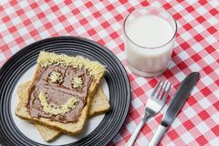Fresh milk with chocolate bread on the table. Top view of fresh milk and chocolate cream spread on bread with funny face above dining table Stock Photo