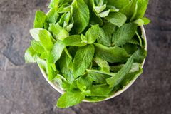 Top view Fresh mint leaves in the ceramic bowl on the dark stone background. Healthy vegetarian food concept. Selective focus. Cop Royalty Free Stock Photography