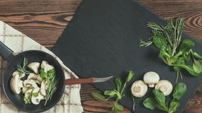 Top view of fresh mushrooms with mash salad and rosemary on a da. Rk frying pan setting on a napkin near black stoned board on a wooden table. Copy space Royalty Free Stock Images