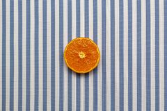 Top view of fresh orange slice fruit on white blue striped background. Minimal style, food concept, flat lay.  royalty free stock photography