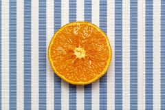 Top view of fresh orange slice fruit on white blue striped background. Minimal style, food concept, flat lay.  royalty free stock photos