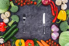 Top view of fresh organic assorted vegetables and fork with knife. On black royalty free stock photo