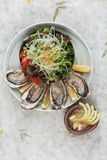 Top view of Fresh oysters and Japanese salad served with Sliced and lemon sauce on white stone bowl on washi Japanese paper.  Stock Photography