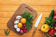 top view of fresh raw healthy vegetables in box and in plate on wooden royalty free stock photos