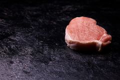 Top view of fresh raw meat on on black wooden table. Gourmet food and fresh uncooked meal Royalty Free Stock Photos