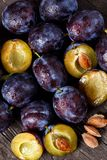Top view on raw plums on wooden table background. Top view on fresh raw plums on wooden table background Royalty Free Stock Photography