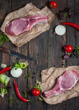 Top view Fresh raw pork neck steak with spices on the kraft paper the dark wooden background. Top view Fresh raw pork neck steak with spices on the kraft paper Royalty Free Stock Photography