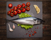 Top View of Fresh Raw Whole Fish Mackerel on Slate Cutting Board. Surrounded by Fresh Herbs and Spices for Seasoning and Garnishing Stock Images