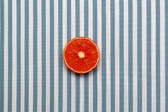 Top view of fresh red orange slice fruit on white blue striped background. Minimal style, food concept, flat lay.  royalty free stock image