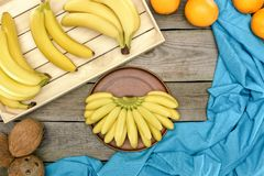 top view of fresh ripe bananas, oranges and coconuts on wooden Royalty Free Stock Photo