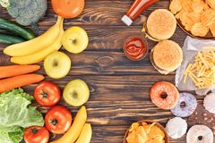 Top view of fresh ripe fruits with vegetables and assorted junk food on wooden. Table royalty free stock photos