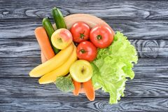Top view of fresh ripe fruits and vegetables on plate. On wooden table royalty free stock images