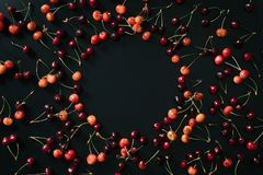 Top view of fresh ripe sweet red and yellow cherries on black background. With copy space Stock Image