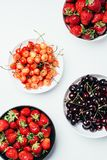 Top view of fresh ripe tasty summer berries in bowls. On white royalty free stock photos