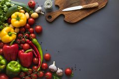 Fresh ripe vegetables with cutting board and knife on grey. Top view of fresh ripe vegetables with cutting board and knife on grey Stock Photo