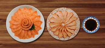Top view of fresh salmon and grill sashimi and shoyu serve on flower shape in white ice bowl boat isolated on wood background, Ja. Top view of fresh salmon and Stock Images