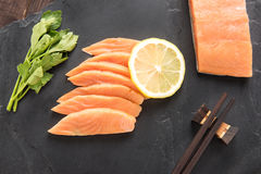 Top view fresh salmon with lemon on black background. Royalty Free Stock Images