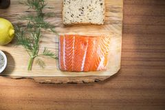 Top view of Fresh salmon steak fillet lying on a wooden plate with a dill, whole wheat bread and lemon Stock Photos