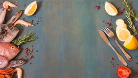 Top view on fresh seafood and fish with fish knife and fork on a blue wooden background with copy space. royalty free stock photography