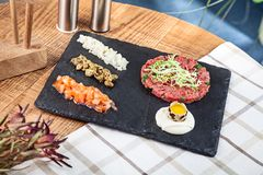 Top view on fresh steak beef tartare served on dark stone plate with sauce and raw quail egg, capers, tomato and chopped onion. Selective focus. Copy space for royalty free stock photography
