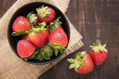 Top view fresh strawberries in a bowl on wooden background. Royalty Free Stock Photography
