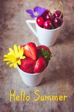 Top view of strawberries, cherries and yellow and purple flowers in bowls on wooden background with a written phrase Hello Summer!. Top view of fresh Royalty Free Stock Photos
