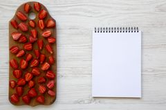 Top view, fresh strawberries on wooden board with blank notebook. Text area. White wooden table. From above. Flat lay stock image