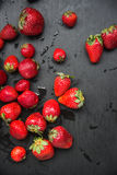 Top view, fresh strawberry harvest nicely scattered on black table Stock Image