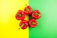 Top view on fresh sweet red pepper. On two colored background in green and yellow Royalty Free Stock Images