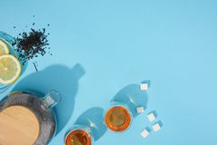 Top view of fresh tea in cups and teapot, sugar cubes, dry herbal tea and sliced lemon on blue royalty free stock images