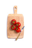 Top view of fresh tomatoes and a knife on chopping board Stock Photo