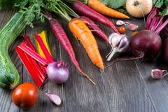Top view of fresh vegetables, spices on rustic dark background. Carrot, beet, chard, zucchini, onion, garlic, tomato. Harvest. Gardening concept Stock Photo
