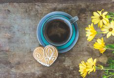 Top view of yellow flowers, blue cup of coffee and a gingerbread cookie on old wooden rustic background Stock Image