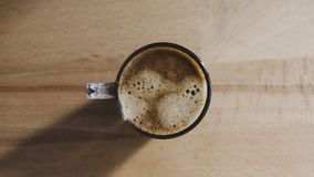 A top view of a freshly brewed coffee. The glass is on top of a wooden platform without other objects around royalty free stock photos