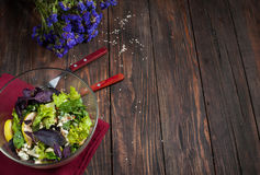 Top view of freshly harvested lettuce, lemon, blue cheese, pearand flowers on an old wood table Stock Photos