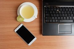 Freshly Lime juice in a white cup, mobile phone, and laptop on wooden floor. Top view, freshly Lime juice in a white cup, mobile phone, and laptop on wooden stock photo
