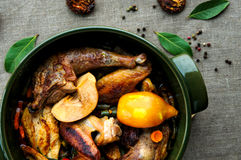 Top view of fried and baked chicken with. Top view of baked chicken with vegetables in round ceramic stew pot on linen fabric background Stock Images