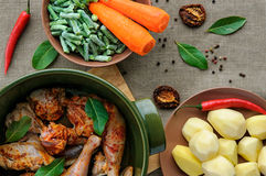Top view of fried and baked chicken with vegetables in round ceramic stew pot on linen fabric background Stock Photos