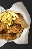 Top view, fried chicken drumsticks, spicy wings, French fries and chicken strips in paper box on black surface, top view. Flat lay. Overhead, from above stock photo