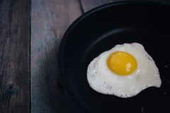 Top view fried eggs in a frying pan on a wooden table. Fried eggs in a frying pan on a wooden table, top view royalty free stock photos